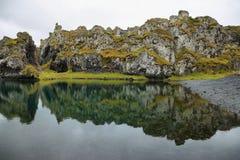 Πράσινη λιμνοθάλασσα στη μαύρη παραλία άμμου Djupalonssandur Στοκ Φωτογραφία
