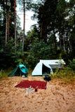 Πράσινη και άσπρη σκηνή που στέκεται σε μια παραλία στη λίμνη Vänern στη Σουηδία με μια σόμπα καλυμμάτων και αερίου μαλλιού και  Στοκ φωτογραφία με δικαίωμα ελεύθερης χρήσης