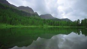 Πράσινη λίμνη στη μέση των ξύλων και των υψηλών βουνών των Άλπεων απόθεμα βίντεο
