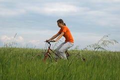 πράσινη οδήγηση κοριτσιών πεδίων ποδηλάτων Στοκ φωτογραφία με δικαίωμα ελεύθερης χρήσης