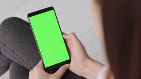 Πράσινη οθόνη στο κινητό έξυπνο τηλέφωνο της νέας γυναίκας στο σπίτι γ απόθεμα βίντεο