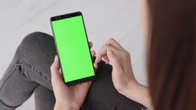 Πράσινη οθόνη στο κινητό smartphone της νέας γυναίκας στο σπίτι για το κλει φιλμ μικρού μήκους
