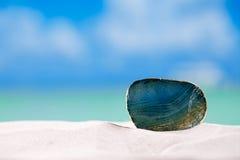 Πράσινη πέτρα γυαλιού στην άσπρη παραλία άμμου, Στοκ Εικόνες