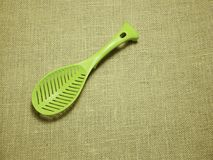 Πράσινη πλαστική κουτάλα υφαμένο στο sackcloth υπόβαθρο στοκ φωτογραφίες
