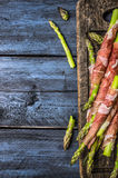 Πράσινη προετοιμασία σπαραγγιού με το ζαμπόν στο σκοτεινό εξεντερίζοντας πίνακα, αγροτικό μπλε ξύλινο υπόβαθρο Στοκ φωτογραφίες με δικαίωμα ελεύθερης χρήσης