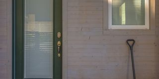Πράσινη πόρτα με το πλακάκι γυαλιού και φτυάρι στον τοίχο στοκ εικόνα