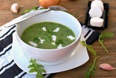 Πράσινη σούπα από το arugula και σκόρδο με το τυρί αιγών στο άσπρο κύπελλο με το κουτάλι στο ξύλινο υπόβαθρο Στοκ Εικόνες