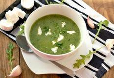 Πράσινη σούπα από το arugula και σκόρδο με το τυρί αιγών στο άσπρο κύπελλο με το κουτάλι στο ξύλινο υπόβαθρο Στοκ Εικόνα