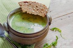 Πράσινη σούπα κρέμας από τα λαχανικά και τα χορτάρια με το ψωμί σε ένα rusti Στοκ Εικόνα