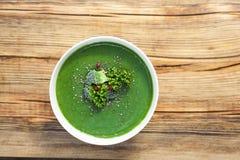 Πράσινη σούπα σπανακιού με το μπρόκολο στο άσπρο κύπελλο στην ξύλινη τοπ άποψη υποβάθρου στοκ φωτογραφίες με δικαίωμα ελεύθερης χρήσης