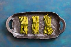 πράσινη συμβολοσειρά φα&sig Πράσινα φασόλια σε ένα κεραμικό πιάτο, μπλε υπόβαθρο Η άποψη άνωθεν, επίπεδη βάζει στοκ εικόνα
