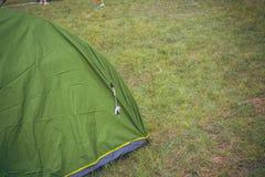 Πράσινη τουριστική σκηνή μεταξύ της χλόης, στο λιβάδι, του δασικού στρατόπεδου Στοκ εικόνες με δικαίωμα ελεύθερης χρήσης