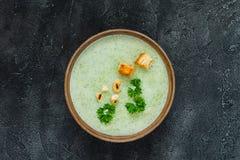 Πράσινη υγιής σούπα κρέμας με το μπρόκολο, κροτίδες, το δυτικό ανακάρδιο, μαϊντανός Τοπ όψη Στοκ Φωτογραφία