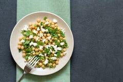 Πράσινη φυτική σαλάτα με chickpeas και το arugula σε ένα άσπρο πιάτο, γκρίζο υπόβαθρο πετρών, τοπ άποψη, διάστημα αντιγράφων στοκ εικόνες