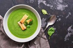 Πράσινη φυτική σούπα κρέμας με το σπανάκι σε ένα σκοτεινό συγκεκριμένο υπόβαθρο Διαιτητικό υγιές μεσημεριανό γεύμα ή γεύμα Τοπ άπ στοκ φωτογραφία με δικαίωμα ελεύθερης χρήσης