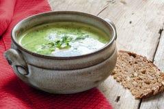 Πράσινη φυτική σούπα κρέμας σε ένα κεραμικό κύπελλο στο αγροτικό ξύλο Στοκ εικόνα με δικαίωμα ελεύθερης χρήσης