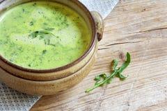 Πράσινη φυτική σούπα σε ένα καφετί κύπελλο στο αγροτικό ξύλο Στοκ φωτογραφία με δικαίωμα ελεύθερης χρήσης