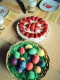 Πράσινη φωλιά με τα ζωηρόχρωμα eastereggs και ένα κέικ φραουλών στο α στοκ εικόνες με δικαίωμα ελεύθερης χρήσης