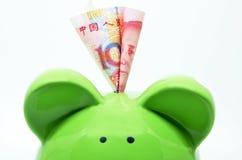 Πράσινη piggy τράπεζα με το νόμισμα της Κίνας Στοκ Εικόνες