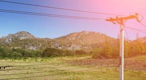 Πράσινοι βουνό και μπλε ουρανός με τις γραμμές δύναμης/τηλεπικοινωνιών Στοκ Φωτογραφία
