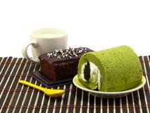 Πράσινοι ρόλοι κέικ τσαγιού και γλυκά κέικ σοκολάτας brownies Στοκ εικόνες με δικαίωμα ελεύθερης χρήσης