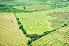 Πράσινοι τομείς και ηλεκτροφόρα καλώδια υψηλής τάσης, άποψη από το αεροπλάνο στοκ φωτογραφία με δικαίωμα ελεύθερης χρήσης
