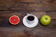 Πράσινοι φρέσκοι μήλο και καφές στο άσπρο φλυτζάνι με το κομμένο γκρέιπφρουτ Στοκ Φωτογραφία