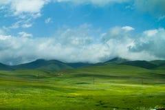 Πράσινοι λόφοι, άσπρα σύννεφα και βουνά στον ορίζοντα Στοκ φωτογραφίες με δικαίωμα ελεύθερης χρήσης