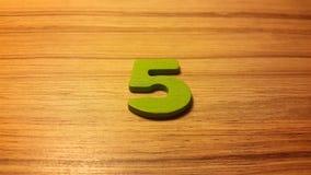 πράσινος αριθμός 5 στο ξύλινο υπόβαθρο Στοκ Εικόνες