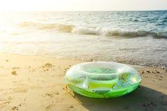Πράσινος διογκώσιμος στρογγυλός σωλήνας στην παραλία άμμου με το φως του ήλιου το βράδυ στοκ φωτογραφίες με δικαίωμα ελεύθερης χρήσης