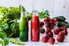 Πράσινος καταφερτζής και καταφερτζής φραουλών σε δύο μικρά μπουκάλια με τα συστατικά σε ένα ελαφρύ ξύλινο υπόβαθρο Υγιές detox Στοκ εικόνες με δικαίωμα ελεύθερης χρήσης
