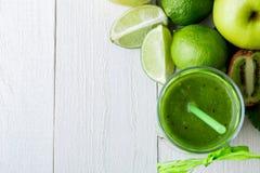 Πράσινος καταφερτζής κοντά στα συστατικά για το στο άσπρο ξύλινο υπόβαθρο Apple, ασβέστης, σπανάκι detox Υγιές ποτό Τοπ όψη Στοκ φωτογραφίες με δικαίωμα ελεύθερης χρήσης