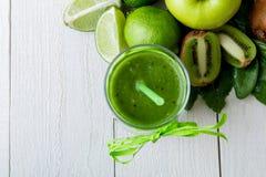 Πράσινος καταφερτζής κοντά στα συστατικά για το στο άσπρο ξύλινο υπόβαθρο Apple, ασβέστης, σπανάκι detox Υγιές ποτό Τοπ όψη Στοκ Εικόνα