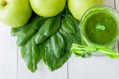 Πράσινος καταφερτζής κοντά στα συστατικά για το στο άσπρο ξύλινο υπόβαθρο Apple, ασβέστης, σπανάκι detox Υγιές ποτό Στοκ φωτογραφία με δικαίωμα ελεύθερης χρήσης