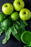 Πράσινος καταφερτζής κοντά στα συστατικά για το στο μαύρο ξύλινο υπόβαθρο Apple, ασβέστης, σπανάκι detox Υγιές ποτό Τοπ όψη Στοκ Εικόνα