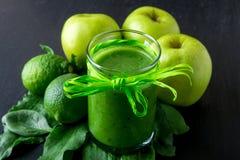 Πράσινος καταφερτζής κοντά στα συστατικά για το στο μαύρο ξύλινο υπόβαθρο Apple, ασβέστης, σπανάκι detox Υγιές ποτό Στοκ Φωτογραφίες