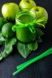 Πράσινος καταφερτζής κοντά στα συστατικά για το στο μαύρο ξύλινο υπόβαθρο Apple, ασβέστης, σπανάκι detox Υγιές ποτό Στοκ Φωτογραφία