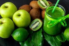 Πράσινος καταφερτζής κοντά στα συστατικά για το στο μαύρο ξύλινο υπόβαθρο Apple, ασβέστης, σπανάκι, ακτινίδιο detox Υγιές ποτό Στοκ φωτογραφία με δικαίωμα ελεύθερης χρήσης