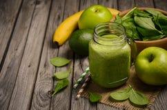 Πράσινος καταφερτζής με το μήλο, την μπανάνα, το αβοκάντο και το σπανάκι σε ένα ξύλινο αγροτικό υπόβαθρο Στοκ φωτογραφία με δικαίωμα ελεύθερης χρήσης