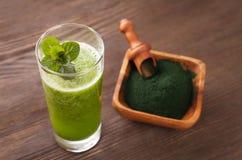 Πράσινος καταφερτζής με το spirulina στο ξύλινο υπόβαθρο στοκ εικόνες