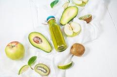 Πράσινος καταφερτζής στο bottl με το αβοκάντο, το μήλο και το ακτινίδιο στο άσπρο ξύλινο υπόβαθρο Στοκ εικόνα με δικαίωμα ελεύθερης χρήσης