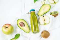 Πράσινος καταφερτζής στο bottl με το αβοκάντο, το μήλο και το ακτινίδιο στο άσπρο ξύλινο υπόβαθρο Στοκ Εικόνες