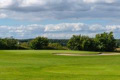 Πράσινος με τη σημαία σε ένα γήπεδο του γκολφ στοκ εικόνες