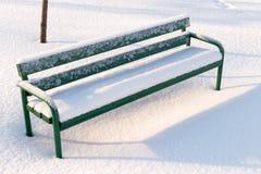 Πράσινος πάγκος σε ένα πάρκο που καλύπτεται με το χιόνι Στοκ εικόνα με δικαίωμα ελεύθερης χρήσης