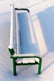 Πράσινος πάγκος σε ένα πάρκο που καλύπτεται με το χιόνι Στοκ Φωτογραφία