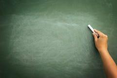 Πράσινος πίνακας κιμωλίας με την κιμωλία εκμετάλλευσης χεριών Στοκ Εικόνες