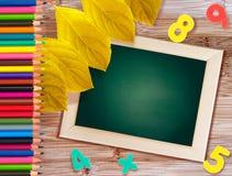 Πράσινος πίνακας με τα πολύχρωμα μολύβια και τους αριθμούς Στοκ Φωτογραφία