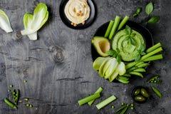 Πράσινος πίνακας πρόχειρων φαγητών λαχανικών με τις διάφορες εμβυθίσεις Hummus, hummus χορταριών ή pesto με τα φρέσκα λαχανικά Στοκ φωτογραφία με δικαίωμα ελεύθερης χρήσης