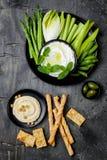 Πράσινος πίνακας πρόχειρων φαγητών λαχανικών με τις διάφορες εμβυθίσεις Σάλτσα γιαουρτιού ή labneh, hummus με τις κροτίδες, ψωμί  Στοκ Φωτογραφία