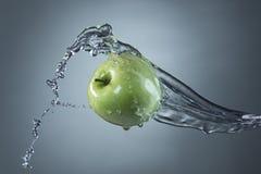 Πράσινος παφλασμός μήλων και νερού στο γκρίζο υπόβαθρο Στοκ φωτογραφίες με δικαίωμα ελεύθερης χρήσης